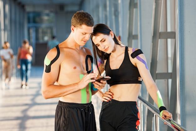 Fit femme brune souriante avec la main sur la taille et l'homme regardant le smartphone et bavardant. athlètes de jeune couple posant à l'intérieur, kinesiotaping coloré sur le corps, intérieur futuriste.