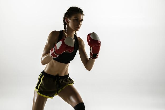 Fit femme caucasienne en boxe sportswear isolée sur mur blanc. formation de boxeuse caucasienne novice et pratique en mouvement et en action. sport, mode de vie sain, concept de mouvement.