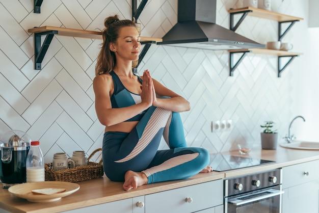 Fit femme caucasienne concentrée assise sur talbe dans la cuisine et méditer.
