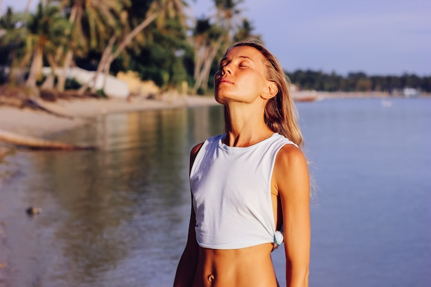 Fit femme caucasienne mince bronzée en haut blanc et culotte bleue au coucher du soleil sur la plage tropicale. femme bronzée en bonne forme profitant du soleil et de l'océan