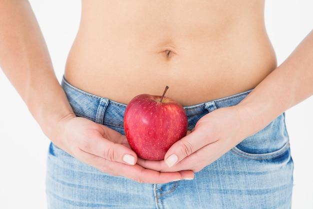 Fit femme debout avec pomme rouge