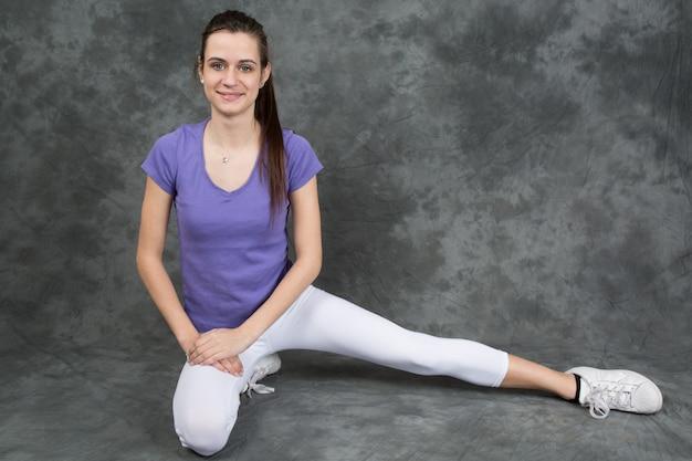 Fit femme étirant sa jambe pour se réchauffer - isolé