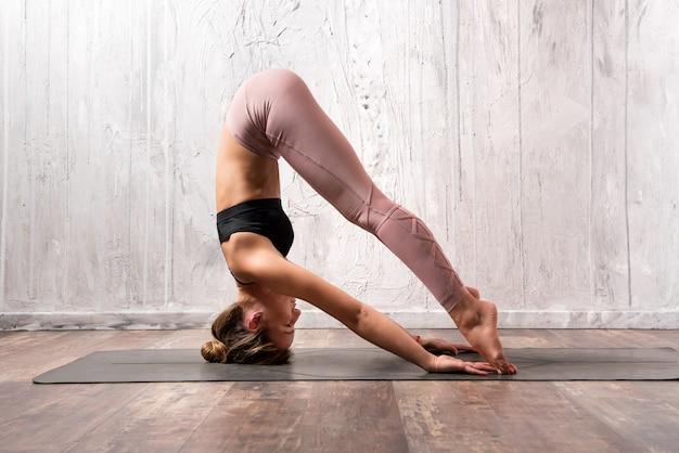 Fit femme exerçant une posture de yoga sirsasana