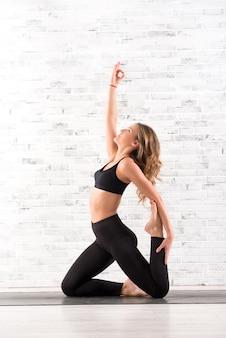 Fit femme faisant ardha dhanhrasana pose de yoga