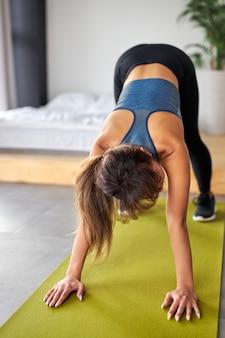 Fit femme faisant des exercices de yoga sur tapis à la maison, portant des vêtements sportifs. mode de vie sain et concept sportif