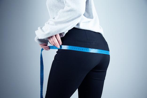 Fit femme mesurant sa taille sur fond sombre