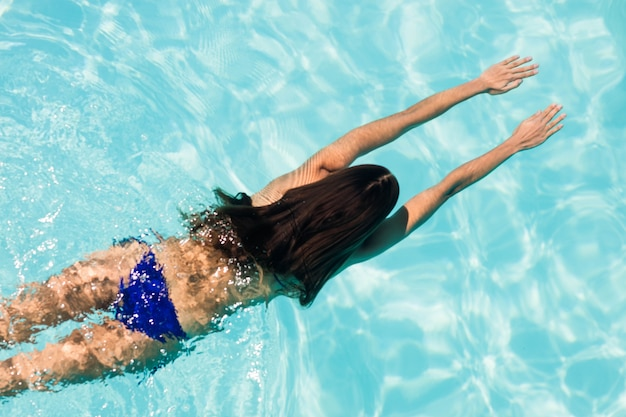 Fit femme nageant dans la piscine dans une journée ensoleillée