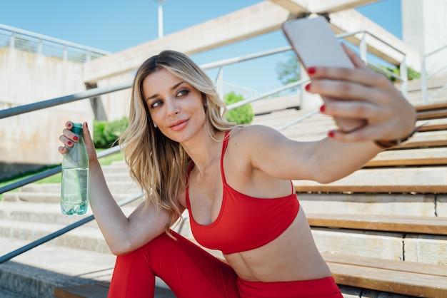 Fit femme prenant un selfie tout en buvant de l'eau
