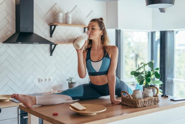 Fit femme prenant son petit déjeuner en position partagée sur la table de la cuisine.
