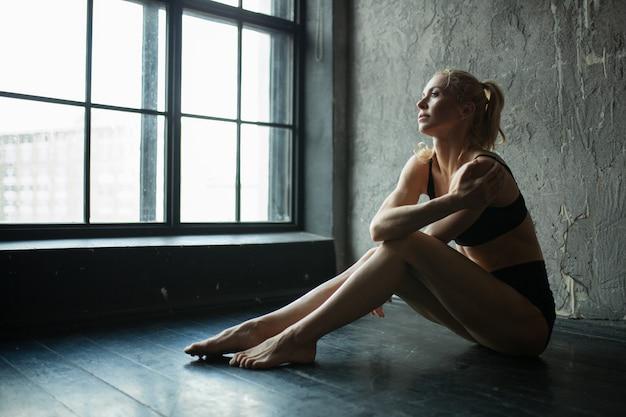 Fit femme de profil assis sur le sol dans la salle de sport loft