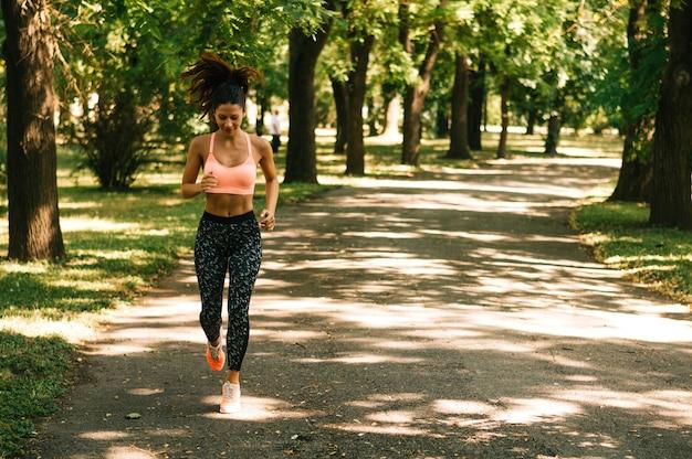 Fit femme qui court à l'extérieur dans le parc par une journée ensoleillée