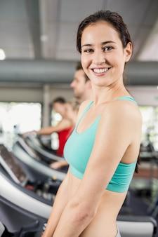 Fit femme qui court sur tapis roulant à la gym