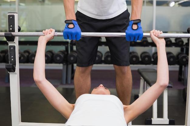 Fit femme soulevant des haltères avec son entraîneur spotting à la salle de gym