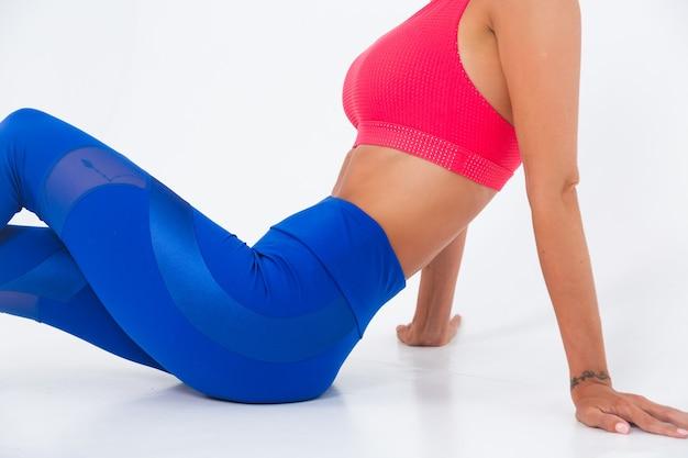 Fit femme sportive bronzée avec des abdominaux, des courbes de fitness, portant des leggings haut et bleu sur blanc