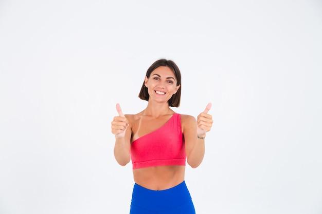 Fit femme sportive bronzée avec des abdos, des courbes de fitness, portant des leggings haut et bleu sur blanc montre les pouces avec le sourire