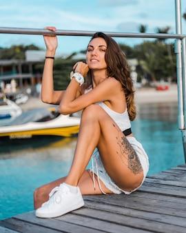 Fit femme tatouée brune tatouée en short en jean bleu clair et haut de montage blanc se trouve sur une jetée en bois au coucher du soleil