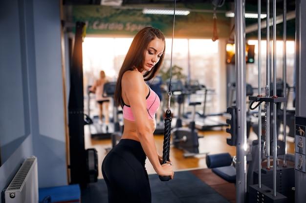 Fit femme triceps d'entraînement soulever des poids dans la salle de gym