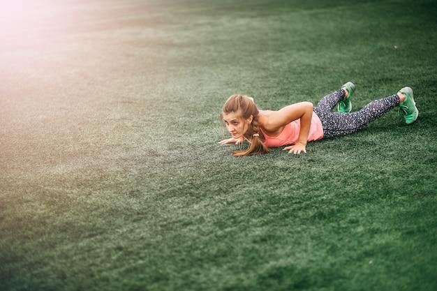 Fit femme en vêtements de sport pour faire des burpees sur l'herbe verte