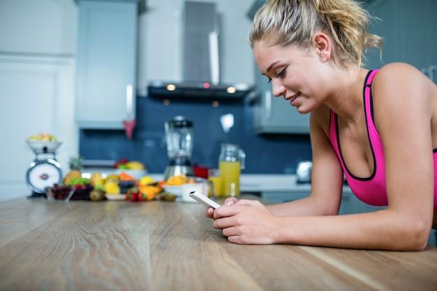 Fit fille envoie des messages texte dans la cuisine