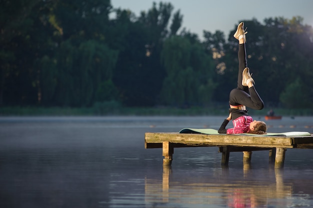 Fit fille faisant des exercices sur la rivière