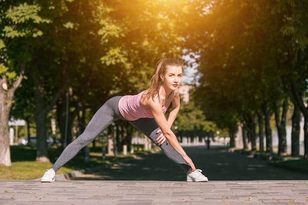 Fit fitness femme faisant des exercices d'étirement en plein air au parc