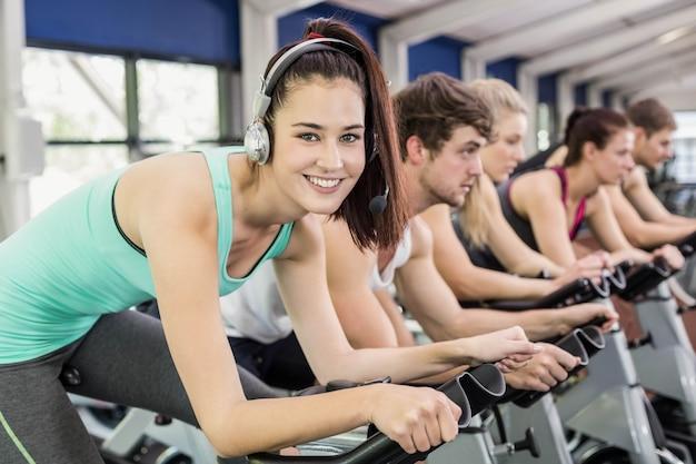 Fit groupe de personnes qui utilisent un vélo d'exercice dans la salle de gym