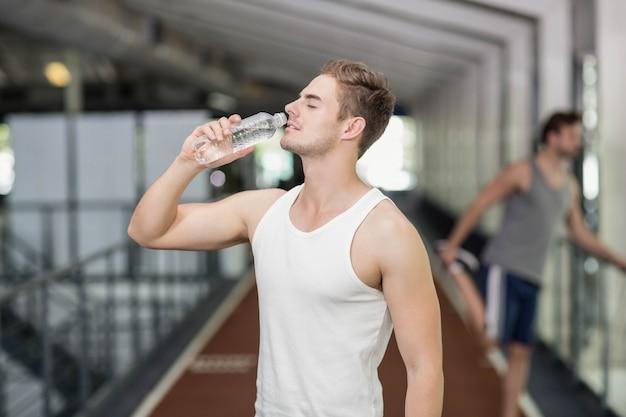 Fit homme de l'eau potable au gymnase de crossfit