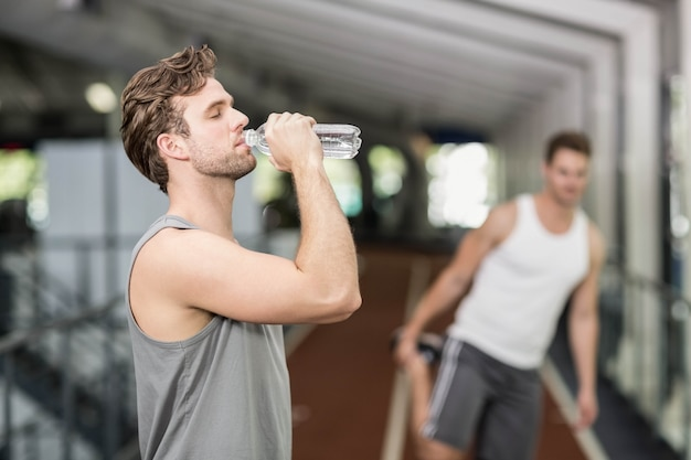 Fit homme de l'eau potable au gymnase de crossfit
