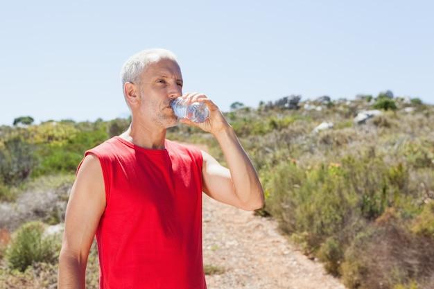 Fit l'homme l'eau potable sur sentier de montagne