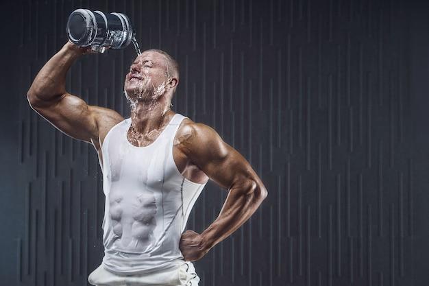 Fit l'homme à l'entraînement dans la salle de gym verser de l'eau sur son visage avec un shaker sur fond sombre