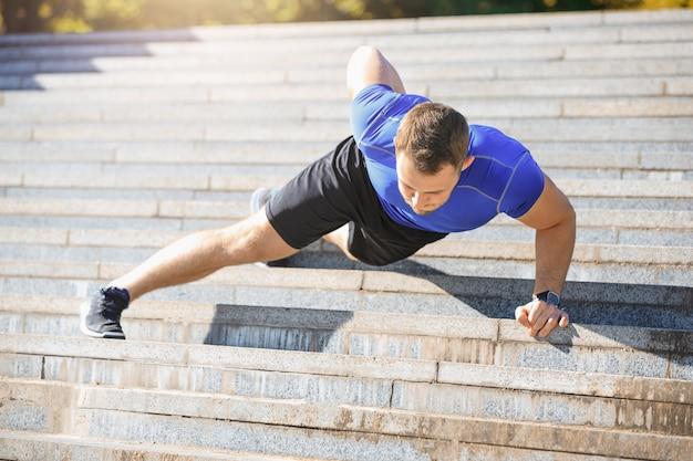 Fit l'homme faisant des exercices à l'extérieur au parc