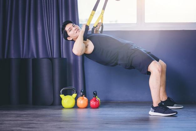 Fit homme faisant des exercices de planche pour la colonne vertébrale dorsale par des push ups avec des sangles de remise en forme de corde dans le gymnase