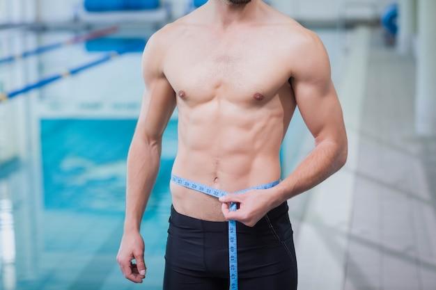 Fit homme mesurant sa taille à la piscine