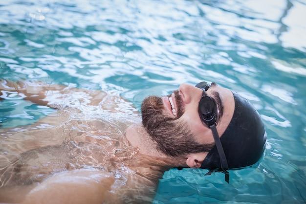 Fit homme nageant sur le dos dans la piscine