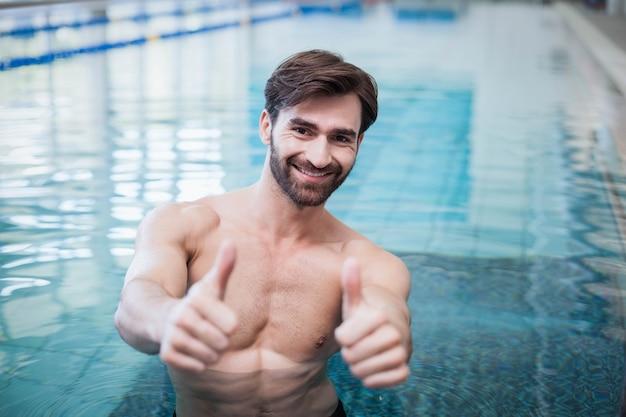 Fit l'homme avec les pouces dans la piscine