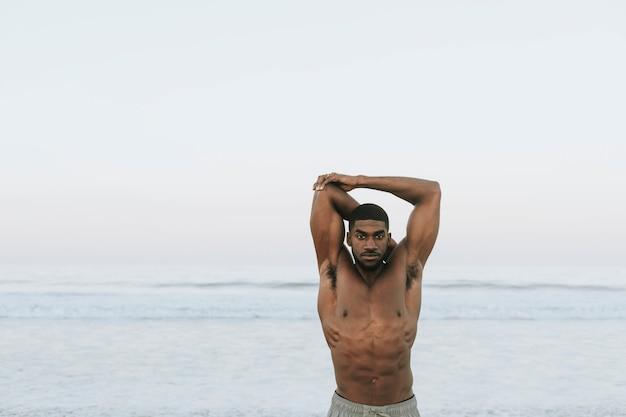Fit homme qui s'étend à la plage