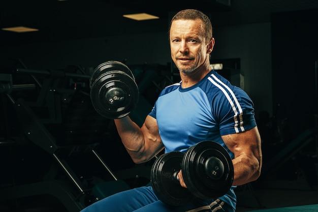 Fit l'homme senior exerçant avec des haltères dans une salle de sport