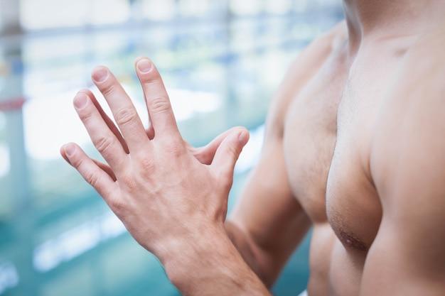 Fit l'homme avec ses mains ensemble à la piscine