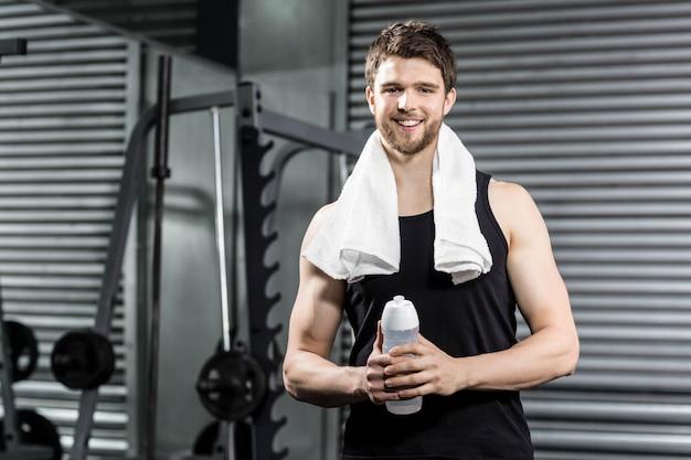 Fit homme tenant une bouteille d'eau au gymnase de crossfit