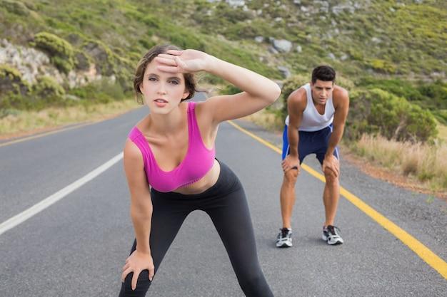 Fit le jeune couple en cours d'exécution sur la route