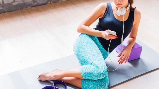 Fit jeune femme assise sur un tapis d'exercice à l'aide d'un téléphone portable