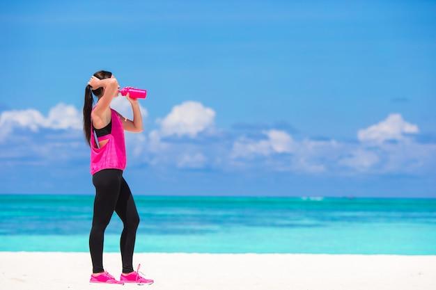 Fit jeune femme boire de l'eau sur la plage blanche