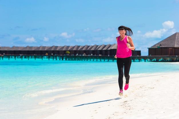 Fit la jeune femme qui court le long de la plage tropicale dans son vêtement de sport