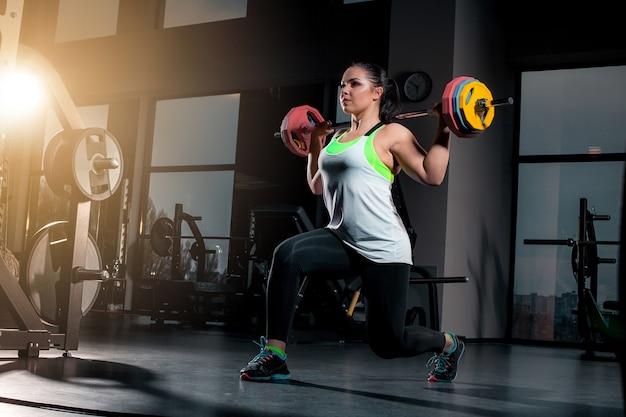 Fit jeune femme soulevant des haltères à la recherche de concentration, travaillant dans une salle de sport