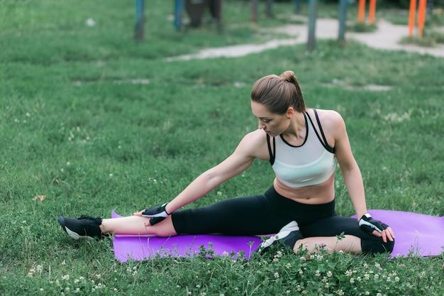 Fit jeune femme en vêtements de sport effectue des étirements après une séance d'entraînement à l'extérieur