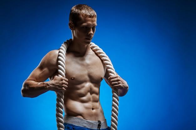 Fit jeune homme avec beau torse et une corde sur un mur bleu