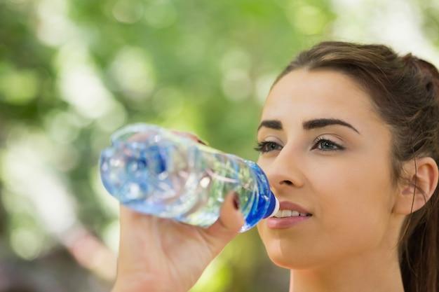 Fit jolie femme buvant à la bouteille de sport