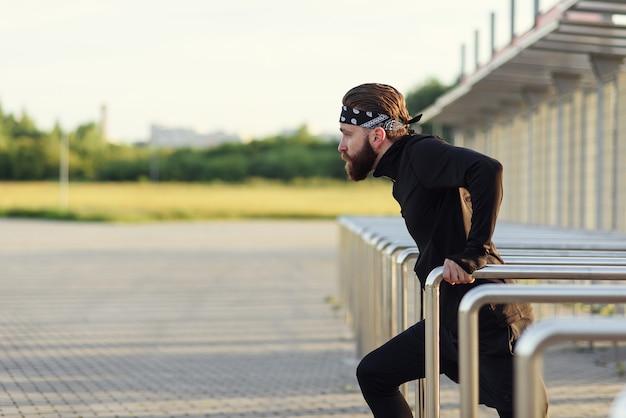 Fit man doing triceps dips sur barres parallèles au parc s'exerçant à l'extérieur
