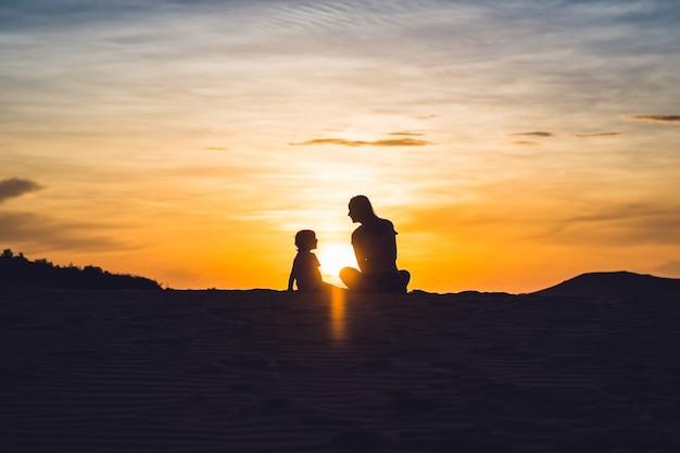 Fit mère avec fils en cours d'exécution dans le désert de gran canaria, maspalomas au coucher du soleil.