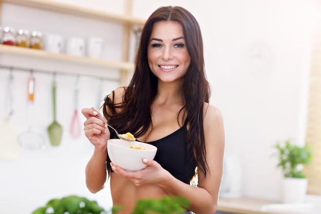 Fit smiling young woman with corn flakes dans la cuisine moderne